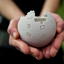 Hands holding Wikipedia world puzzle